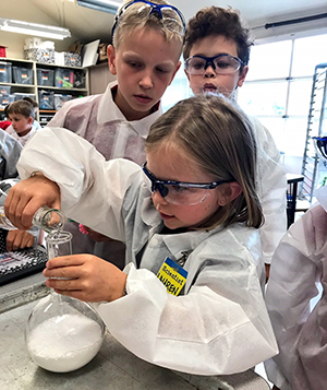 Girl pouring material into beaker in classroom
